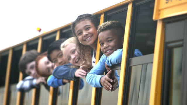 elementary school children looking out bus window waving - first day of school stock videos & royalty-free footage