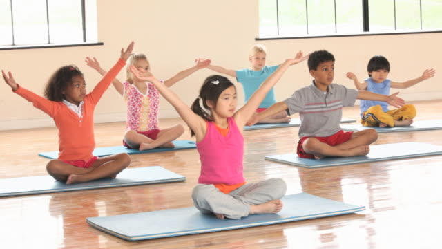 WS Elementary School children practicing yoga, meditation in gym / Richmond, Virginia, United States