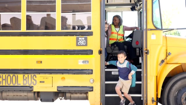 elementary school children unload bus - first day of school stock videos & royalty-free footage