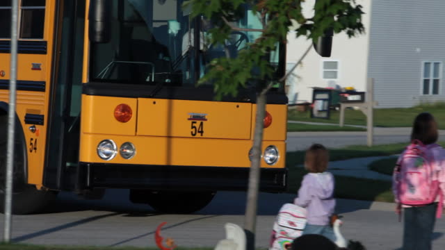 Elementary school children wait for a school bus in Indianapolis, Indiana.