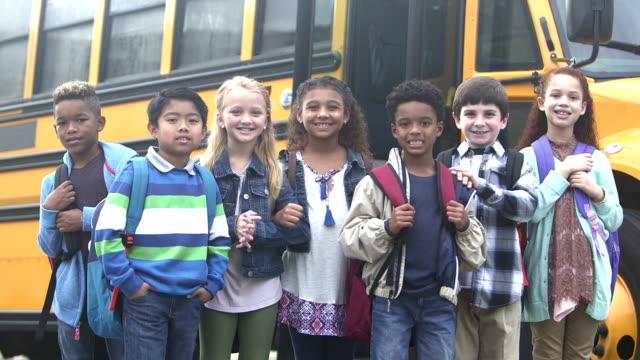 Elementary school children waiting outside bus