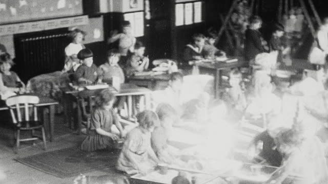 1925 PAN Elementary school classroom bustling with activity including students playing in sandbox, riding rocking horse, and swinging in swing boat / Newcastle upon Tyne, England, United Kingdom