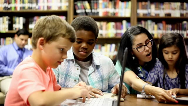 elementary school counselor with students in library. - elementary student stock videos & royalty-free footage
