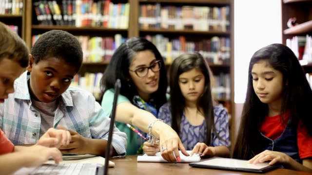 elementary school counselor with students in library. - group therapy stock videos & royalty-free footage
