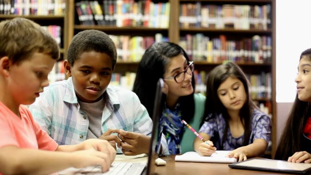 elementary school counselor with students in library. - alternative therapy stock videos and b-roll footage