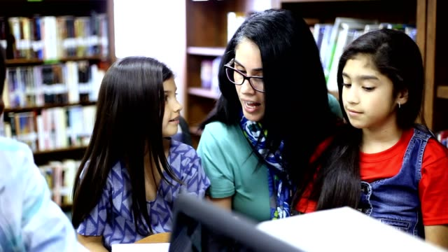elementary school counselor with students in library. - mental health professional stock videos & royalty-free footage