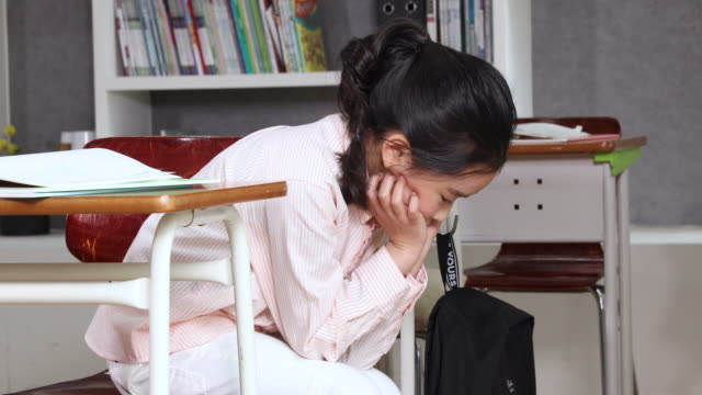 elementary school girl sitting in depressed posture - hand on chin stock videos & royalty-free footage