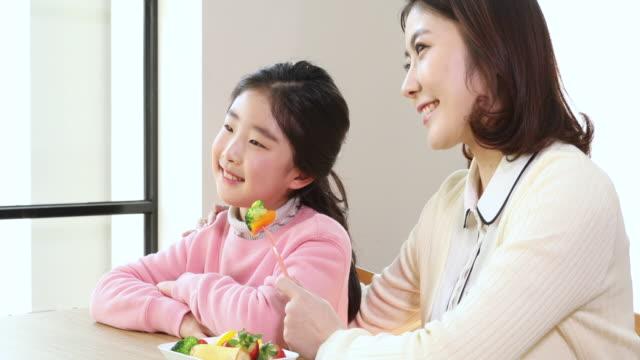 vídeos de stock e filmes b-roll de elementary school girl smiling and teacher with vegetable in her hand - professora