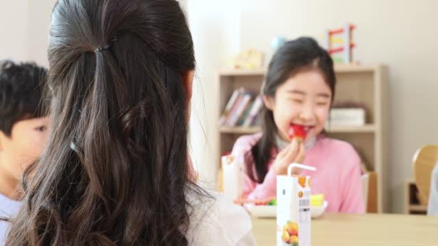 vídeos de stock e filmes b-roll de elementary school girl who likes strawberry taste - merenda escolar