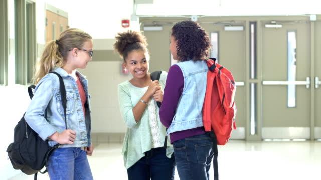 elementary school girls conversing in hallway - rucksack stock videos & royalty-free footage