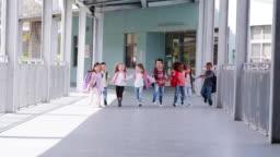 Elementary school kids run holding hands in school corridor