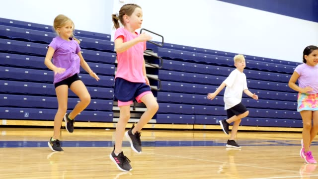 elementary school students exercise during pe class - elementary age stock videos & royalty-free footage