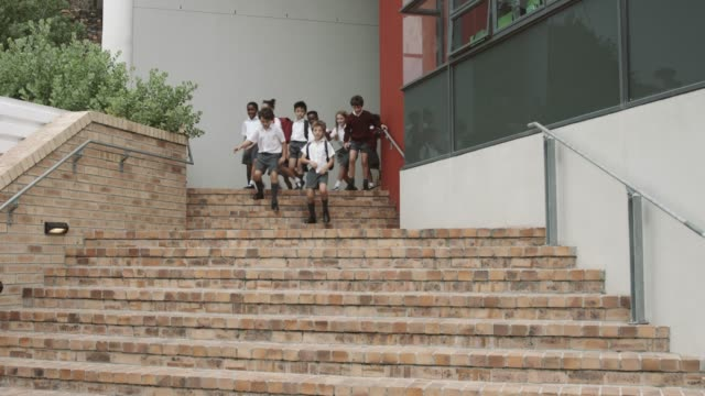 vídeos de stock, filmes e b-roll de elementary school students moving down on steps - ir embora
