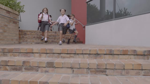 elementary school students moving down on steps - steps and staircases stock videos & royalty-free footage