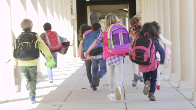 elementary school students running towards school - rucksack stock videos & royalty-free footage