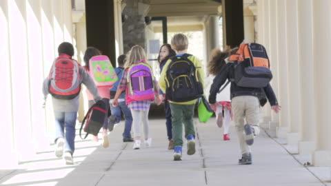 stockvideo's en b-roll-footage met elementary school students running towards school - rugzak