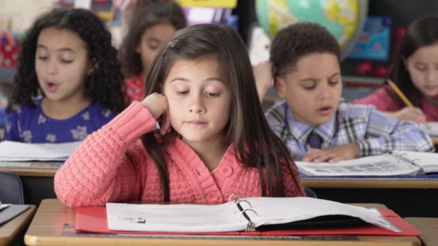 vídeos de stock e filmes b-roll de elementary school students studying in classroom - escola primária