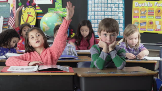 elementary school students with hands raised in classroom - educazione video stock e b–roll