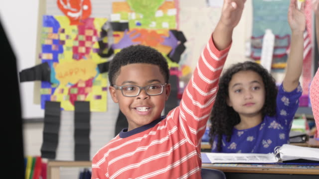 Elementary school students with hands raised in classroom