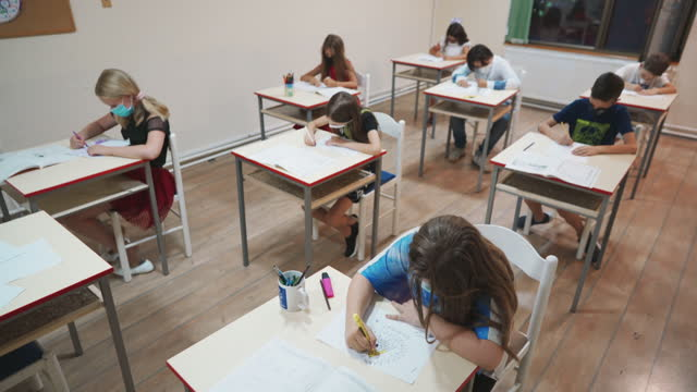 elementary school students with protective face masks drawing on the art class in the elementary school - art class stock videos & royalty-free footage