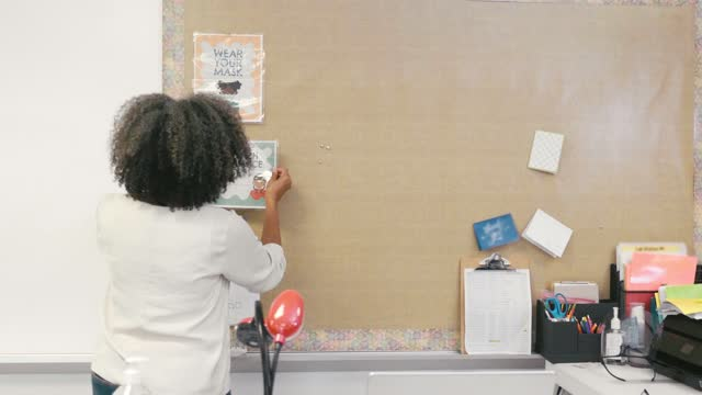 vidéos et rushes de un enseignant de l'école primaire raccroche des pancartes en classe sur un comportement approprié pendant covid-19 - panneau d'information