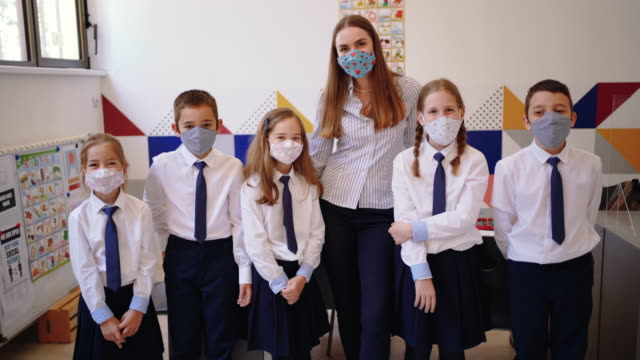 elementary school teacher posing with her students with a face masks on - primary school child stock videos & royalty-free footage