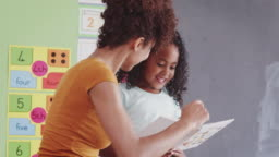 Elementary School Teacher Reading With Female Pupil In Classroom Giving One To One Support