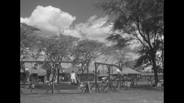 elementary school-age children play on swing sets in community of model homes operated by the sugar planters association for its workers; some of the... - altalena video stock e b–roll