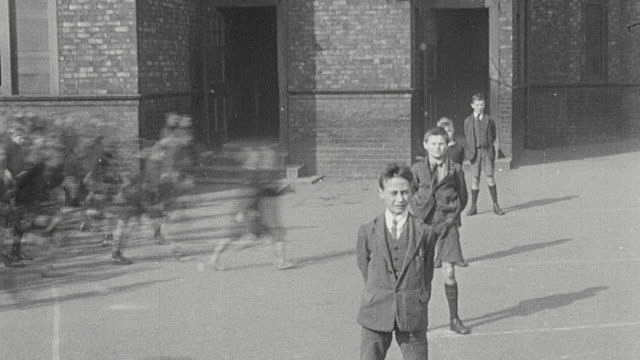 1925 MONTAGE Elementary schoolboys playing on school grounds rapidly forming into columns and marching into the school building / Newcastle upon Tyne, England, United Kingdom