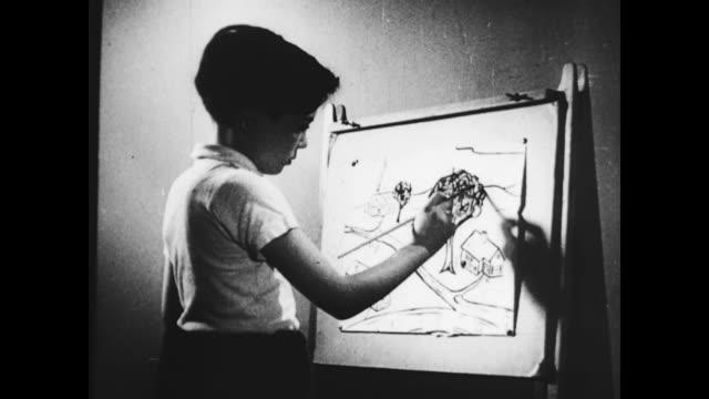 vidéos et rushes de / elementary schoolchildren painting at easels / boy painting piece of pottery / boy painting picture of suburban neighborhood scene / suburban... - élève du primaire