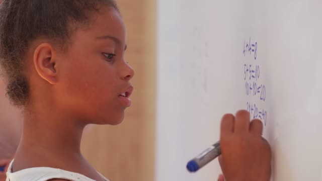 stockvideo's en b-roll-footage met basisschoolmeisje dat wiskunde met een leraar op whiteboard doet - plusteken