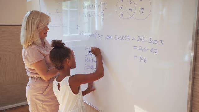elementär skolflicka gör matematik med en lärare på whiteboard - förklara bildbanksvideor och videomaterial från bakom kulisserna