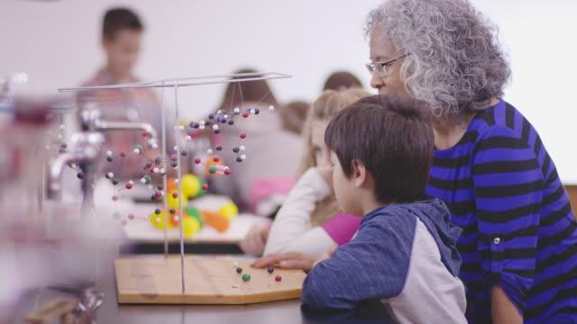 Elementary Science Class with Nurturing Older Teacher