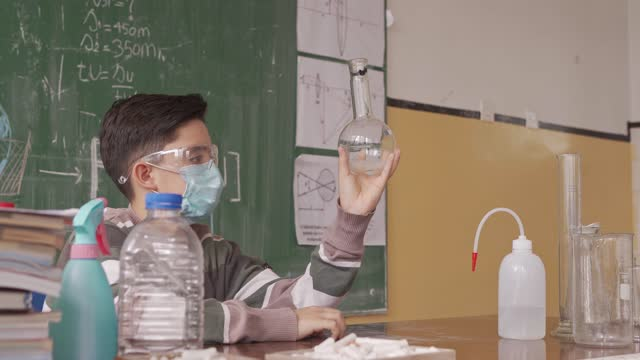 elementary student performing his chemistry experiment in his classroom wearing protective eyeglasses and face mask - brainstorming stock videos & royalty-free footage