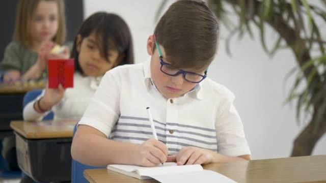 vidéos et rushes de étudiants élémentaires faisant l'activité de groupe dans la salle de classe - reprise des cours