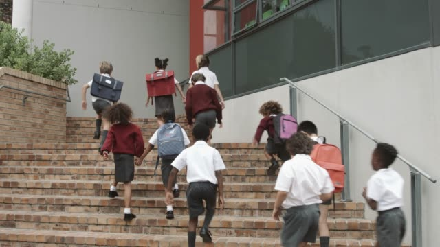 elementary students entering school building - educazione video stock e b–roll