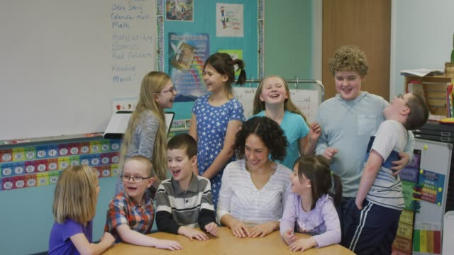 Elementary Students Gathered Around Their Teacher and Laughing