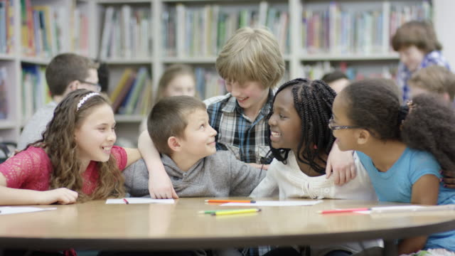 Elementary students hanging out together in library looking at camera