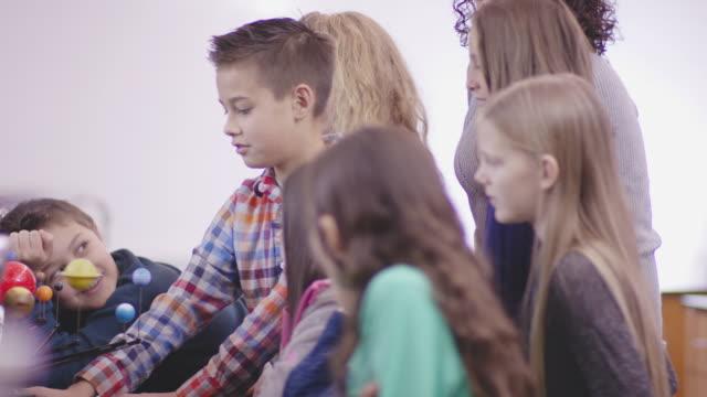 stockvideo's en b-roll-footage met elementaire studenten die studeren astronomie en planeten in het lab van een klasse met de hulp van hun etnische rijpe leraar. - fatcamera