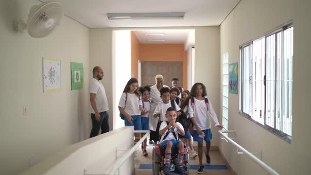vídeos de stock, filmes e b-roll de alunos do ensino fundamental caminhando no corredor da escola e abraçando professor na escola - respect