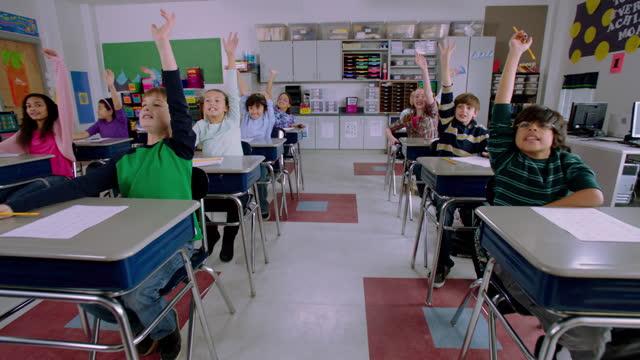 vídeos y material grabado en eventos de stock de elementary students wave their hands, hoping to be called on during class. - niño pre escolar