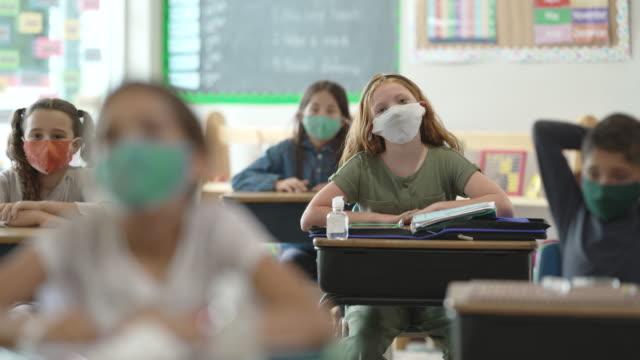 grundschüler tragen masken im unterricht - multi ethnic group stock-videos und b-roll-filmmaterial