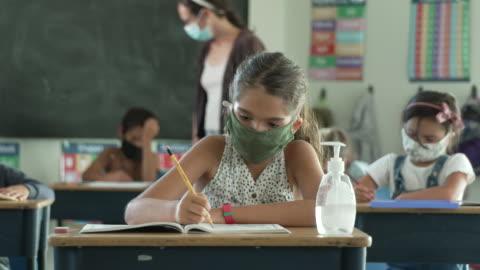 elementära studenter bär masker i klassrummet - skolbyggnad bildbanksvideor och videomaterial från bakom kulisserna
