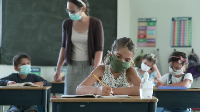 elementary students wearing masks in the classroom - insegnante video stock e b–roll