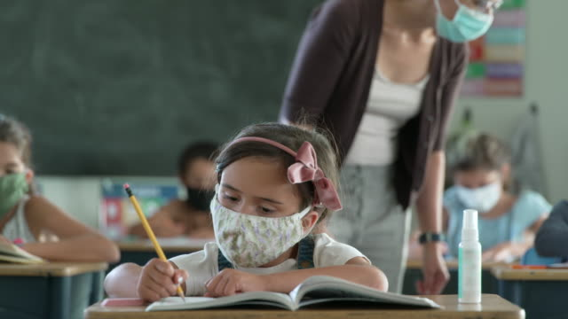 elementary students wearing masks in the classroom - aula video stock e b–roll