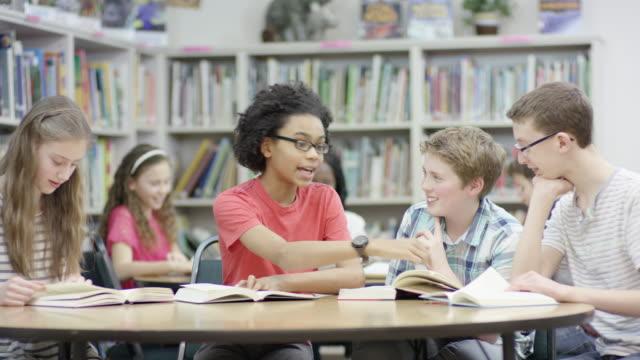 elementare studenten, die arbeiten in der bibliothek - gemischte altersgruppe stock-videos und b-roll-filmmaterial