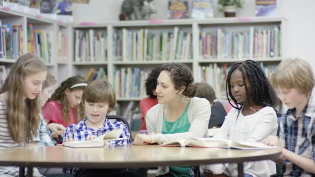 elementare schüler arbeiten mit lehrer in der bibliothek - gemischte altersgruppe stock-videos und b-roll-filmmaterial