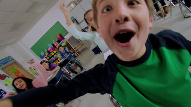 elementary students yell and cheer at their desks during class. - klassenzimmer stock-videos und b-roll-filmmaterial