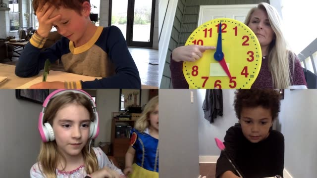 vídeos de stock, filmes e b-roll de elementary teacher explains how to read a clock as her young students take notes via video call. (audio) - aprendizagem online