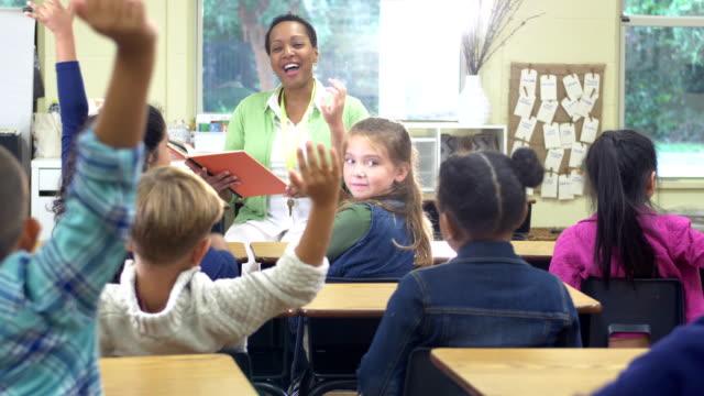 elementär lärare, multietniska barn som höjer händerna - 6 7 years bildbanksvideor och videomaterial från bakom kulisserna